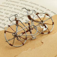 """Made by hand in Kisumu, Kenya, from recycled copper and steel wire, our jaunty little pin is for cyclists and global citizens. About 2""""w x 1""""h. Safety pin back. Sales of this Fair Trade product benefit young women in Kenya."""