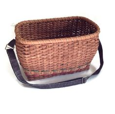 Vintage woven carrying basket. Wooden strips with a small fish design along the bottom. The basket has a brown fabric carrying strap which