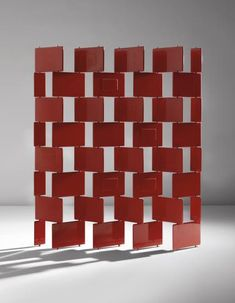 """EILEEN GRAY Unique """"Brick"""" screen designed 1922-1923, executed 1973 Red lacquered wood, steel, brass. Each large brick: 8 5/8 x 12 5/8 x 1/2 in. (21.9 x 32.1 x 1.3 cm) 71 1/4 in. (181 cm) high Variable width, as shown: 59 in. (149.9 cm) Lacquer executed by Pierre Bobot, Paris."""