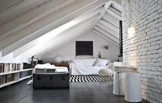 l'arredo di una mansarda, le travi in legno dipinte di bianco danno la percezione di uno spazio più grande.