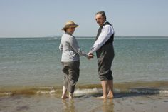Mrs. Hughes and Mr. Carson of Downton Abbey holding hands on the beach at the edge of the ocean  .