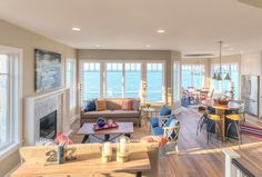 Open Layout Interiors. Tall windows and ceilings flood the main floor with natural light, while white oak floors set the stage for a happy color palette with pops of red and blue. The end result is a relaxed and livable space that remains classic to the core. Mike Schaap Builders
