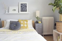 "so many elements i love in this room - the gray and yellow combo; the quilt combined with more modern elements; mismatched bedside ""tables"""