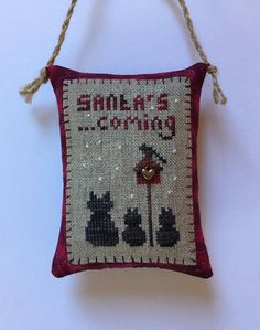 """Completed primitive cross stitch SA ta's coming Christmas Ornament Its hand cross stitched by me on 30 ct natural linen with DMC and overdyed floss, backed with cotton, stuffed with new non-allergenic polyester and decorated with a heart charm and jute hanger Size is ~ 3,5x4,5"""" not"""