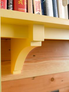 Custom-made corbels support a cookbook shelf in this kitchen hutch built-in. Fir paneling behind it helps the yellow paint pop and ties in the built-in with the rest of the cabinetry.