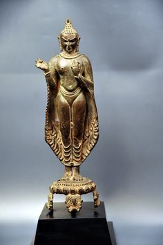 Standing Pagan Buddha. Country: Burma, circa 13th century Height: 42 cm. Round base. Material: Copper alloy. Standing bronze Buddha image wearing a silk cloth which softly covers the whole body. The hands are in teaching mudra, face in very strong expression.
