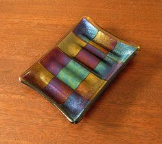 A rainbow of shimmering metallic squares are set against a light amber background in this handmade fused glass dish. This art glass dish is large enough to hold oversized French milled soaps. Subtle ridges in the bottom help to keep your soap out of waters way. Or set small tea light candles on this dish and let the soft candle light reflect off of the dish surface for a romantic evening setting.  This glass has been kiln fired twice: once to create its geometric pattern and again to create…