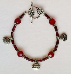 This Love, Courage and Hope charm bracelet is made to remind you of your inner strength. Three 1/2-inch silver-plated charms--Love, Courage and Hope--dangle from the bracelet made with genuine garnet cylindrical beads and four 8mm garnet Swarovski crystals, which are flanked by filigreed silver bead caps. A round, floral toggle clasp completes the piece, which measures 7.5 inches