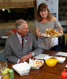 Prince Charles, Prince of Wales and Camilla, Duchess of Cornwall are served fish and chips in Aberdaron during a visit to the Welsh Village on July 5, 2016 in Aberdaron, England. The Prince Charles, Prince of Wales and Camilla, Duchess of Cornwall are on the second day of their annual visit to Wales. - Prince Of Wales & Duchess Of Cornwall's Annual Summer Visit To Wales