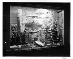 """The window display features several differing types of hunting rifles, and men's hunting clothing with accessories. Affixed to the rear of the display is a scene of two men sitting in a canoe, hidden in the reeds; one has his rifle aimed at the fowl in the sky above. Signage affixed in the foreground of the window reads, """"1881, The J.L. Hudson Company's Sixtieth Jubilee Year, 1941."""""""