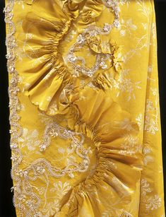 Detail decoration, robe à la francaise (sack-back gown), England, 1760-1765. Yellow and white woven silk with a pattern of floral trails including honeysuckle and rosebuds, trimmed with silk fly fringe, lined with linen.