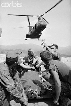 03 Mar 1969, A Shau Valley, South Vietnam --- 3/3/1969-A Shau Valley, South Vietnam: U.S. Marines give plasma to a wounded comrade struck down during fighting along South Vietnam's border with Laos. American troops located an unusually large store of enemy weapons during a raid along the border.