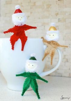 Pipe cleaner Santa Claus ornaments - Red, green, and gold. Use a small spun cotton egg for the head. These cute little guys can be twisted and bent any way you like - a fun DIY project for Christmas and the Holidays.