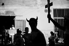 """Christopher Anderson  VENEZUELA. Caracas. 2006. A man in a devil costume runs around the streets of La Vega before a rally for Chavez. The act is to make fun of the idea of the """"red devil of socialism."""""""