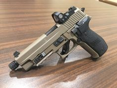 the Sig RX. It's a tactical model of the venerated Sig so the platform is as solid as it gets. The RX starts with the standard railed adds Sig Night sights, a tan Cerakote finish, and gets finished with a Reflex red dot sight. Tactical Pistol, Tactical Gear, Tactical Survival, Weapons Guns, Guns And Ammo, Samurai Weapons, Revolver, Sig Sauer P226, Sig P229