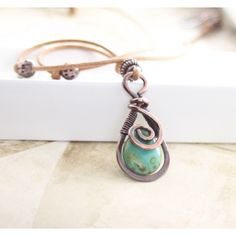 Handcrafted copper necklace in swirly drop design with teal Picasso Czech glass briolette on almond brown leather cord