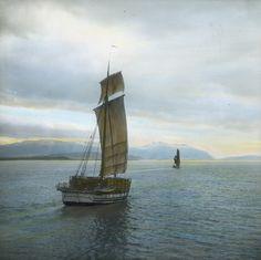 Jakt og jakt [?] sydover  Håndkolorert dias. To seilbåter av typen jakt seiler ved kysten.