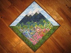 Lake Tahoe is known for its blue skies, pine trees and mountains. This landscape art quilt features the view from the Lake - a meadow of flowers