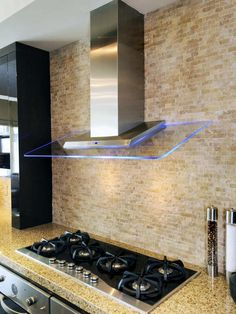 Natural Stone Tile Backsplash - Contrasts w/ the modern cabinetry and professional grade appliances. Also check out that Glass Range Hood! Very modern!
