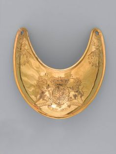 Gilt brass gorget worn by Captain Sir Francis Carr Clerke, 3rd Regiment of Foot Guards, 1777 (c) Carr Clerke (1748-1777) was killed at Saratoga in 1777, during the American War of Independence (1775-1783), while serving as aide-de-camp to Major-General John Burgoyne.  Crescent-shaped gorgets of silver or silver gilt were worn by officers in most European armies, both as a badge of rank and an indication that they were on duty;  discontinued by the British army in 1830.