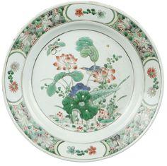 Plat peint dans les émaux de la famille verte en porcelaine de Chine de la Compagnie des Indes d'époque Kangxi Petit plat peint dans les émaux de la famille verte décoré au centre d'un oiseau et d'un papillon parmi des fleurs de lotus. L'aile est cantonnée de quatre cartouches sur un fond pointillé de branchages fleuris. A l'arrière, marque au double cerclage.