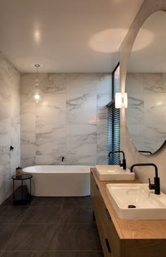 The bathroom features marble, wood and black tapware. A giant circular mirror…