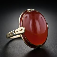 Art Deco 10.40 ct Carnelian Ring with enameled frame. 14K yellow gold with white gold chevrons on each shoulder. Circa 1930s