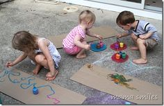 Painting sheets of cardboard outside - creative summer fun!
