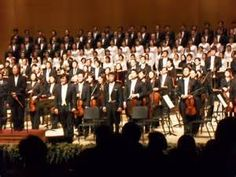 End of a concert. Tenor Na Seung seo and the orchestra bering applauded. He is standing with his hands at his side, wearing white tie and tails, his usual concert style of dress.