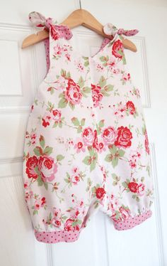 This vintage traditional & classic style romper has the beautiful Cath Kidston rose fabric print on both the front & back, which ties on each shoulder to fasten. It is fully lined with Cath Kidston shabby chic pink spotty fabric and contrasting leg cuffs at knee length.  It is a very roomy & comfortable style, so perfect for fitting a nappy under and easy movement for rolling, crawling & toddling. Very easy & quick to get on and off.  ***please note the lining on the rompe...