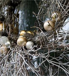 Outdoor porch decorations for Christmas in silver and gold. With a homemade twig wreath for the front door. See more details at www.songbirdblog.com