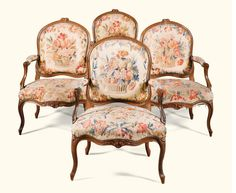 A set of four carved walnut armchairs, Louis XV, circa 1750 each with arched moulded top-rails carved with flowers, downswept arms and serpentine seats and cabriole legs, covered with late 18th/early 19th century floral Aubusson tapestry.