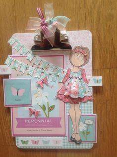Altered clipboard with prima doll and pebbles garden party paper collection.