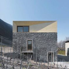 Geneva studio clavienrossier created this home in the Swiss Alps by adding two tinted concrete volumes atop the remains of a stone house and adjacent barn