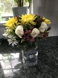 Spring flowers w yellow chrysanthemums in rectangular container.