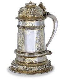 Lot Description AN ELIZABETH I PARCEL-GILT SILVER TANKARD LONDON, 1581, MAKER'S MARK GA Slightly tapering cylindrical on domed circular foot and with moulded ribs, the hinged domed cover and scroll handle with cast cartouche thumbpiece, finial lacking, engraved and chased with strapwork, fruit and flowers, the body later engraved with presentation inscription and date