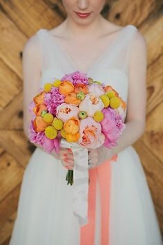 A vibrant arrangement with roses, peonies, and billy balls complement the bride's coral sash.Photo Credit: Dave Richards Photography on Dave Richards via Lover.ly