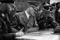 German Chancellor and dictator Adolf Hitler consults a geographical survey map with his general staff including Heinrich Himmler (left) and Martin Bormann (right) at an undisclosed location in 1939. (AFP/Getty Images).