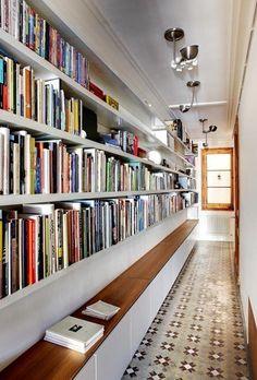 Interessante biblioteca feita no corredor com piso de ladrilho hidráulico.