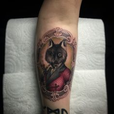 Wolf in a smoking jacket. Cameo frame colour tattoo. Done by Adam Thomas from Marked One Tattoo & Gallery