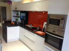 See how the orange glass backsplash gives the white cabinets an injection of colour!