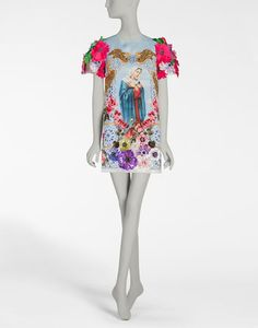 <i>The Spring-Summer 2017 is a journey towards an imaginary Italian Tropic, where the icons traditionally associated with Italy, like bread, pasta and good luck charms are merged with a holiday atmosphere, punctuated by cocktails, ice cream and sequins.</i><br><br>A-line dress in triple silk organza featuring a religion-inspired print, embellished by beautifully hand-embroidered designs and decorative bejeweled buttons on the back:<br>• Round neck<br>...