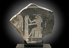 Relief, probably from a naos, depicting the god Khnum fashioning mankind (and all living creatures) with clay on his potter's wheel  Highly polished granite  32,5 x 35,5 cm  Egypt, 30th dynasty, 380-343 BC