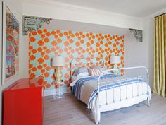 An old-fashioned iron bedstead gets a boost from a bold, modern wallpaper. Design by Home by Novogratz