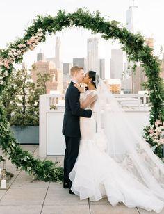 Rooftop NYC Summer Wedding // modern giant floral wreath wedding ceremony backdrop new york city skyline nyc