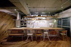 plafond en béton, parquet et support à vaisselle suspendu dans la cuisine de style industriel contemporaine