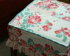 Such a cute idea! A Slipcover for her ottoman made from a vintage tablecloth!