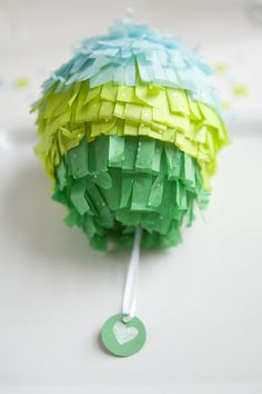a piñata for everyone? cuter than this of course. if its a dinner party, maybe just hanging over their plates unexplained- a surprise snack and a garland in one!