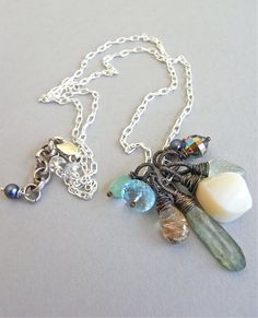 "The Seascape necklace - a gorgeous array of gemstones, a lone pearl and a dazzling vintage crystal have been wrapped, heavily oxidised and then suspended from bright sterling chain.  Adjustable and long line - extends to 23""."