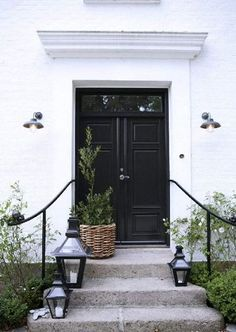 Front stoop styling | Place lanterns on steps and a potted tree next to the front door for a polished look